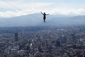 آلکساندرشولتز بین دو ساختمان بلند در مکزیک در حال بند بازی است