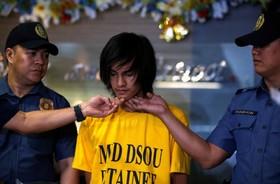 پلیس در مانیل چهره محمد اومااو را به عنوان متهم سوم در بمب گذاری علیه سفارت آمریکا در مانیل را به خبرنگاران نشان می دهند