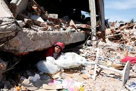 مردی در ماردو در آچه اندونزی از خرابه های زلزله اخیر پنکه هایی را از یک مغازه بازیابی می کند