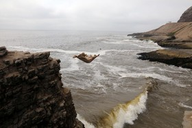 یک شناگر از یک سخره در ساحل هرادورا در لیما در پرو به دریا می پرد