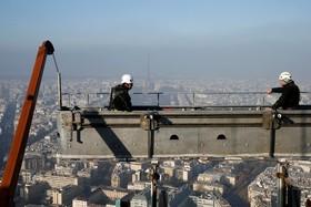 کارگران مشغول پاکسازی شیشه های یک برج و در افق برج ایفل در مه دود گم شده است