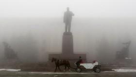 یک درشکه چی در حال عبور از میدانی با مجسمه ولادیمیر لنین در اساوروپول در روسیه
