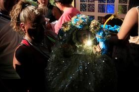 زنی در مراسم مذهبی پایان سال نو مجسمه ای نمادین از کودکی عیسی مسیح را در دست دارد