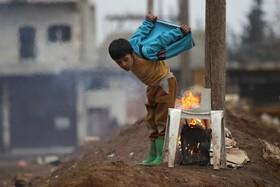 کودک سوری آواره خودرا گرم می کند