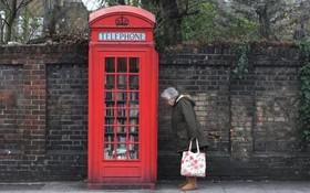 زنی در کنار یک کیوسک تلفن که به کتابخانه تبدیل شده است