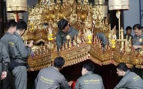 گروهی از کارکنان درحال آماده سازی وسیله انتقال جسد پادشاه تایلند به مدفن