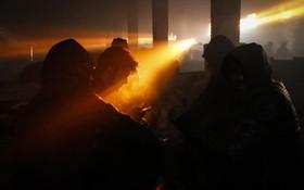 گروهی از مهاجران در بلگراد در یک خانه مشترک در حال گرم کردن خویش با آتش