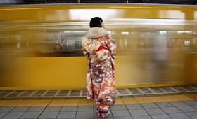 خانمی که درچشن بیست سالگی شرکت کرده با لباس سنتی در ایستگاه مترو در توکیو