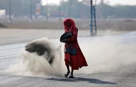یک زن کارگر در حال پاشیدن خاک نرم بر روی خیابانی که تازه آسفالت شده است