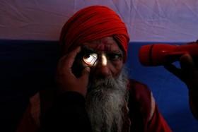 یک روحانی هندو در حال انجام معاینه چشم پیش از عزیمت به فستیوال مذهبی ماکار ساکرانتی در کلکته