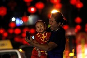 سلفی مادر کودک در خبان تزئین شده از چشن سال نو چینی در یانگون میانمار