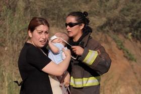 یک آتش نشان در حال بستن ماسک برای کودکی که مادرش اورا در آغوش دارد پس از نجات از آتش سوزی جنگل در شیلی