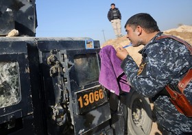 یک سرباز عراقی در جنگ در موصل در حال ریش تراشی