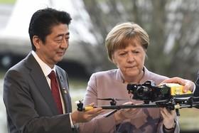 شینزو آبه نخست وزیر ژاپن و آنگلا مرکل صدر اعظم آلمان در نمایشگاه بزرگ کامپیوتر و نرم افزار هانور آلمان موسوم به سی بیت در حال مشاهده یک هواپیمای بدون سرنشین