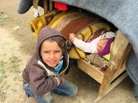 مصطفی چهارساله در کار نگهداری از برادر کوچکترش در اردگاه آوارگان در حمام علی در حومه موصل