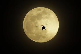 پرواز یک هلیکوپتر در آسمان لاس وگاس در مقابل ماه کامل