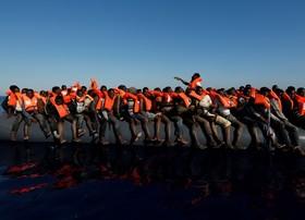 گروهی از مهاجران غیرقانونی در دریای مدیترانه نزدیکی سواحل لیبی در انتظار کمک