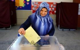 یک زن با حجاب در ترکیه در حال رای دادن در جریان رفراندوم در ترکیه