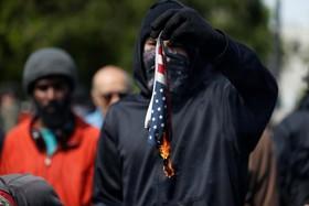 تظاهرات و درگیری حامیان و مخالفان ترامپ در آمریکا:یک مخالف دونالد ترامپ پرچم آمریکا را آتش می زند
