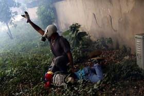 کمک یکی از تظاهرکنندگان مخالف دولت مادورو در کاراکاس در ونزوئیلا به تظاهرکننده دیگر که در این تظاهرات زخمی شده است