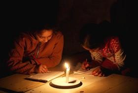 دانش آموزان فلسطینی در اردگاه محل اقامت خود در خان یونس به دلیل قطع برق در نور شمع درس می خوانند