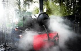 راننده لکوموتیو بخار که به تازگی بین استگاه هایی کوتاه در انگلیس راه اندازی شده در حال روغن کاری چرخ ها