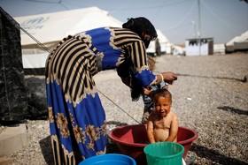 کودک آواره عراقی در حومه موصل در حال حمام