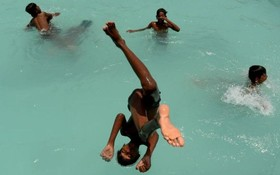 کودکانی که در چنای هند از گرمای هوا آب تنی می کنند