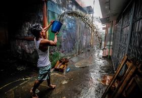 تلاش یک مرد برای خاموش کردن آتش سوزی در خیابانی در مانگوا در نیکاراگوئه