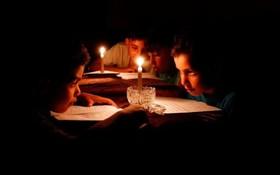 درس خواندن کودکان فلسطینی در زیرنورشمع به دلیل محدودیت برق در غزه