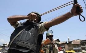 یک پلیس ضد شورش هند در سرینگر با تروکمان در مقابل تظاهرکنندگان کشمیری