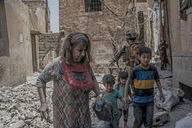زنی به همراه فرزندانش در حال ترک محل درگیری میان ارتش عراق و داعش در موصل