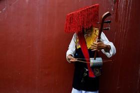 یک نوازنده در در کاتماندو نپال درحال آماده شدن برای اجرای برنامه در جشن تولد دالای لاما رهبر مذهبی تبت