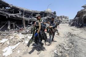 سربازان عراقی در حال حمل کمربندهای انتحاری پیدا شده از مراکز داعش در موصل