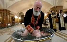 غسل تعمید یک کودک در کلیسایی در تفلیس تاجیکستان