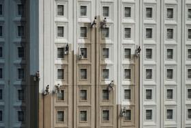 کارگران در حال رنگ کردن نمای یک برج در پکن چین