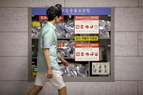 ایستگاه مترو در سئول کره جنوبی و رهگذری که از مقابل ویترین وسایل ضروری و اولیه برای آمادگی در صورت وقوع جنگ احتمالی با کره شمالی در ایستگاه برای پناه گرفتن مردم آماده شده است