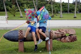 کودکان در حال بازی در پارکی کنار یک بمب باقیمانده از زمان جنگ دوم جهانی درجزایرگوآم در اقیانوس آرام که کره شمالی تهدید به حمله اتمی به پایگاه آمریکا در این جزیره کرده است