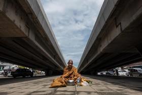 روحانی بودایی در کنار خیابانی در بانکوک تایلند در حال جمع آوری خیرات