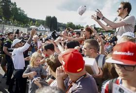 لوئیز همیلتون قهرمان رانندگی در بلژیک در حال عکس انداختن با طرفدارانش و امضای یک کلاه برای یک طرفدار