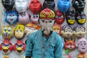 ماسک فروشی در کنار خیابان در حیدرآباد هند و ماسک یک خدای هندو بر صورت یک نوجوان