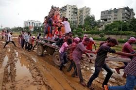 حمل مجسمه گانوش در فستیوال گانوش در احمد آباد هند در زمینی گل آلود در باران های موسمی