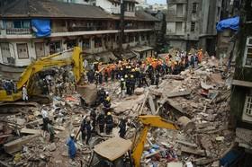 نیروهای امدادی در حال بررسی منطقه ای که ساختمان ها به دلیل باران های سیل آسا فرورخته است