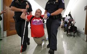 پلیس نابینایی را که در اعتراض به تغییر قانون بهداشت عمومی در کنگره در میان تظاهرکنندگان بوده را از راهرو کنگره خارج می کند