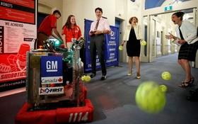 جاستین ترودو نخست وزیر کانادا در کنار مشاور علمی و وزیر علم در نمایشگاه دانشجویی فناوری های جدید در جال آزمایش یک ربات پرتاب کننده توپ