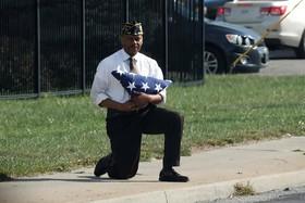 مرد نظامی سابق در کنار خیابنی که کاروان خودرو دونالدترامپ رئیس جمهوری آمریکا از آن می گذرد با زانو زده است.