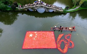 کشاورزی چینی با ماهی های قرمز پرچم چین را به مناسبت شصت و هشتمین سالگرد تشکیل این جمهوری در رودخانه در روستای ویون ساخته است