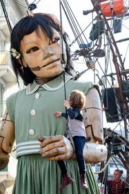 کودکی با مجسمه دختر غول پیکر که در سوئیس در نمایشی خیابانی به همراه مارد بزرگ و سگش حرکت می کند بازی می کندت