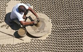 مردی در حال ساختن ظرف های گلی کوچک در اجمر در هند