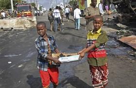 کمک کودکان به پاکسازی منطقه ای در سوالی که در آن محل انفجار رخداده است